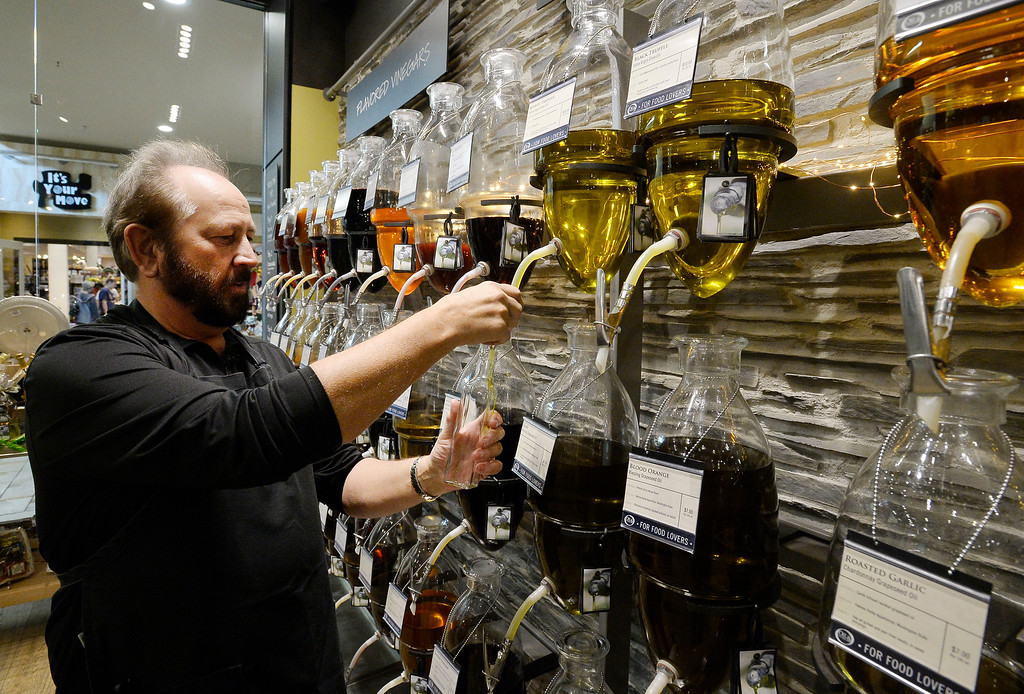 . BROOMFIELD, CO - November 23, 2018: Dave Setter, owner of Oil & Vinegar, fills a bottom for the sample dishes. Cleveland Creek (furniture/furnishings store) and Oil and Vinegar, both at Flatiron Crossing Mall, are getting ready Friday for Small Business Saturday.  (Photo by Cliff Grassmick/Staff Photographer)