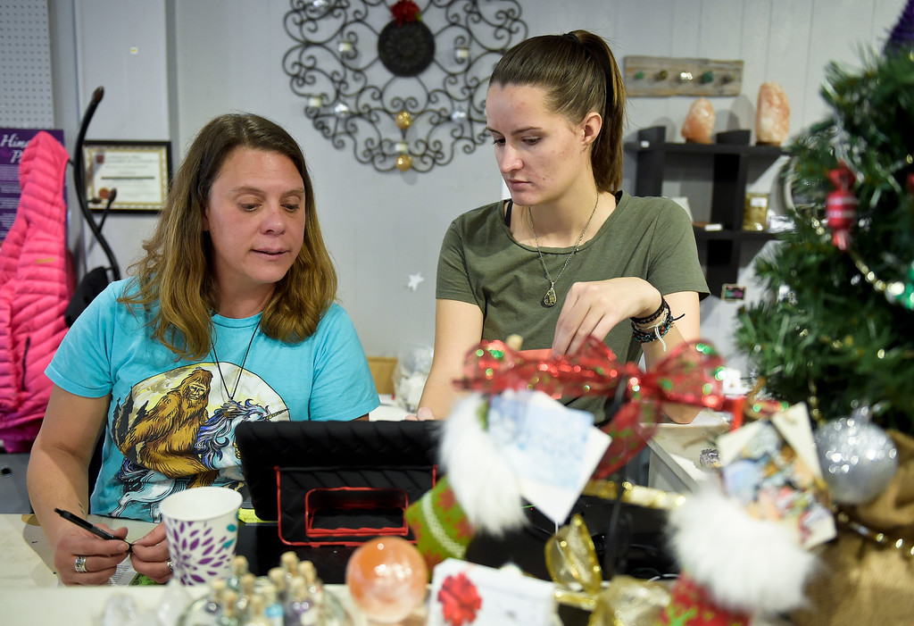 . LONGMONT, CO - NOVEMBER 23: Nichole Case helps coworker Claudia Hahn with the cash register at Crystal Joys Nov. 23, 2018. Crystal Joys is located at 340 Main St., Longmont. (Photo by Lewis Geyer/Staff Photographer)