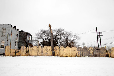 A city still run down, covered by fields and abstract pastels of weathered paint, Detroit.