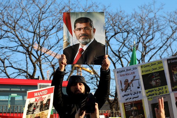 London / UK – January 20, 2020: A protestor holds a picture of former Egyptian President Mohamed Morsi during a protest by the UK Africa Investment Summit in London, where his successor Abdel Fattah El-Sisi was speaking