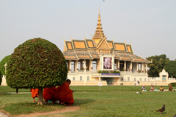 Monks rest in the shade of a bush in the Royal Palace in Phnom Penh, Cambodia