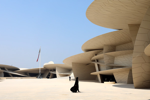 Doha / Qatar – September 30, 2019: A local woman walks through the main courtyard of the National Museum of Qatar