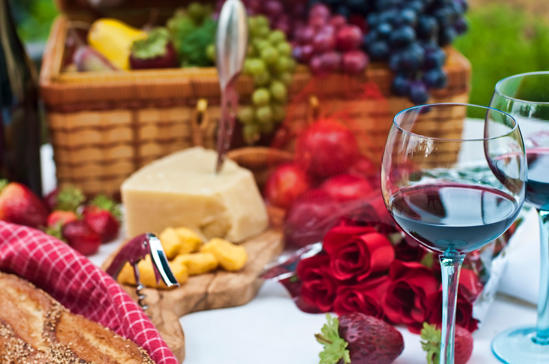 Picnic basket filled with fresh fruit, cheese, bread, wine for two.