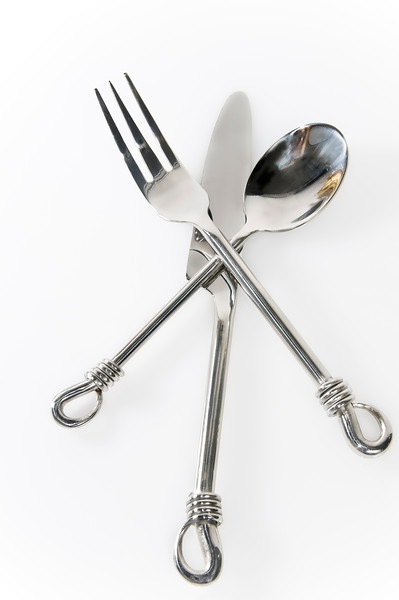 spoon, knife and fork shot on white reflective surface