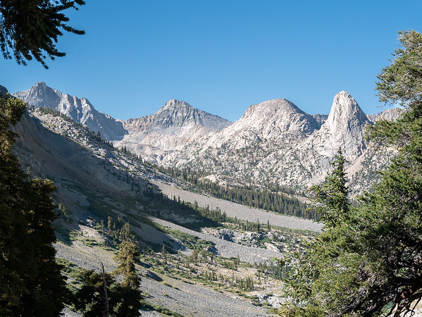 """Then the trail turns a corner and goes up rise ... and to this splendid view up the South Fork of Woods Creek opens up.   From L to R, Dragon Head Painted Lady, and unnamed 11960' mound, and Fin Dome.  Less splendid is the route ahead: lots of medium size rocks (4-12"""") to scramble through."""
