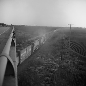 2018.008.CNW.FD.277--bruce meyer 120 neg--C&NW--EMD diesel locomotives on freight trains meeting at speed action--east of Maple Park IL--1974 0713