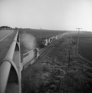 2018.008.CNW.FD.276--bruce meyer 120 neg--C&NW--EMD diesel locomotives on freight trains meeting at speed action--east of Maple Park IL--1974 0713