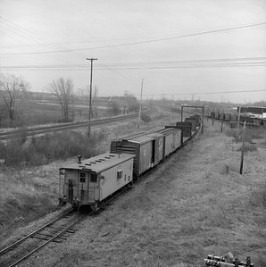 2018.008.CNW.FD.281--bruce meyer 120 neg--C&NW--caboose on hind end of local freight train scene--west of West Chicago IL--1975 0128