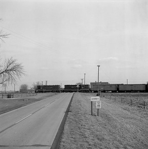 2018.008.IC.FD.1883--bruce meyer 120 neg--ICRR--EMD diesel locomotive 9161 on northbound freight train crossing highway scene--Leverett IL--1958 0313