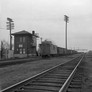 2018.008.IC.FD.1874--bruce meyer 120 neg--ICRR--caboose on hind end of southbound freight train passing interlocking tower--Champaign IL--1958 0308