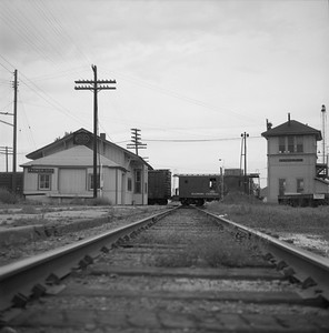 2018.008.IC.FD.1936--bruce meyer 120 neg--ICRR--caboose on southbound freight train 63 passing interlocking tower and depot--Farmer City IL--1958 0524