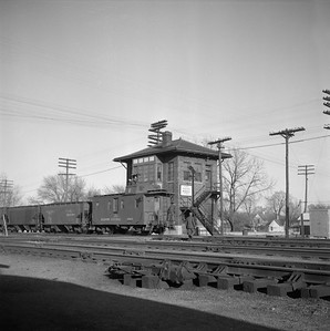2018.008.IC.FD.1504--bruce meyer 120 neg--ICRR--caboose on freight train passing interlocking tower--Champaign IL--1957 1219