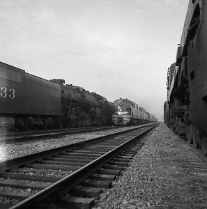 2018.008.MP.PD.004--bruce meyer 35mm neg--MP--EMD diesel locomotive 7017 on eastbound passenger train 12 Colorado Eagle passing AT&SF and GTW steam locomotives--Kansas City MO--1960 0407