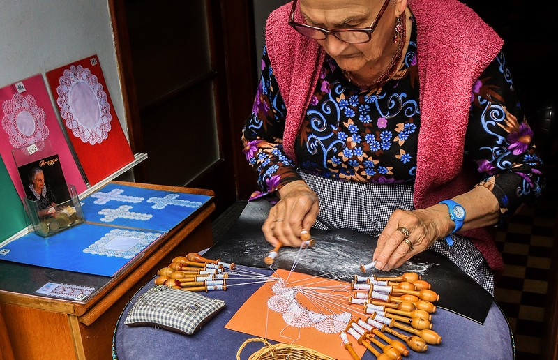 Woman giving a lace making demonstration  for donations. Each bbbin must be moved a certain way in a certain sequence to get the pattern right.