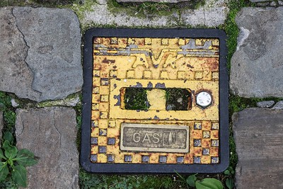 Cast iron gas valve covers dot the streets and lower sections of building walls throughout Bruges, belgium.