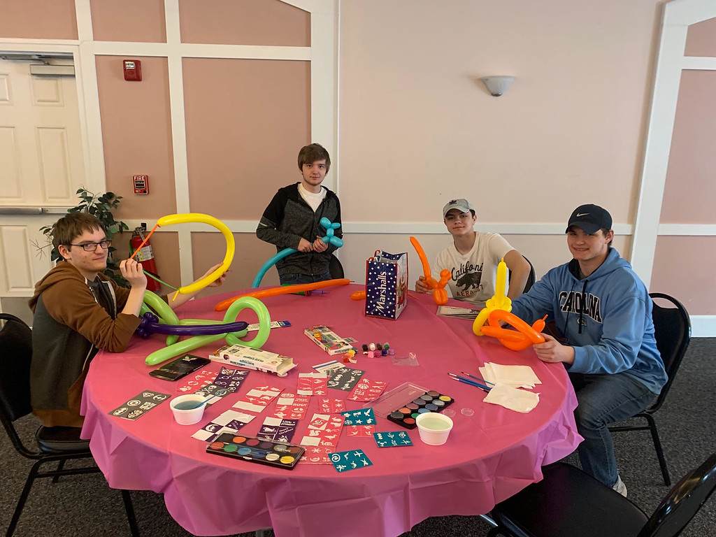 . Young men volunteer for arts and crafts and balloons.