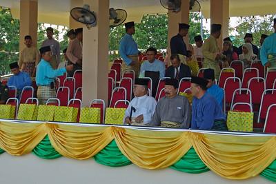 Die ersten geladenen Gäste nehmen Platz. In den gelben Tüten sind die Gastgeschenke. Die Tribünen sind nagelneu.