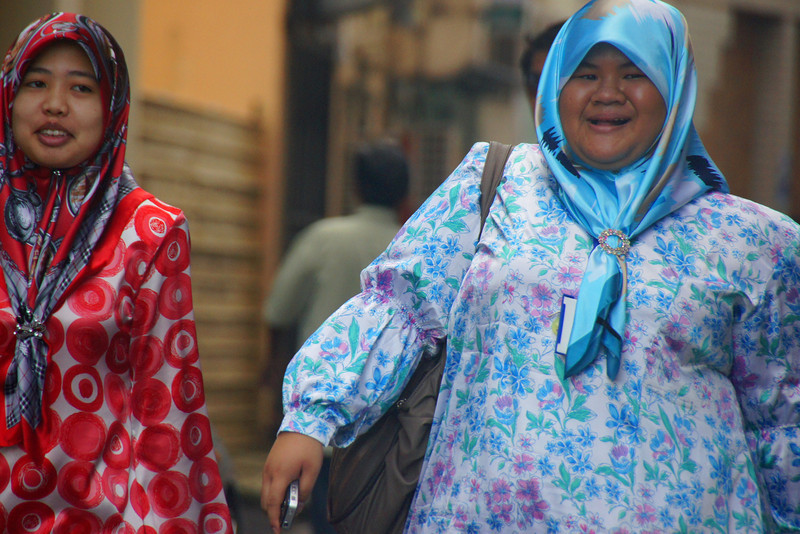 Today's daily travel photo is of two Brunei ladies wearing brightly colored clothing walking down the street in downtown Bandar Seri Begawan, Brunei.
