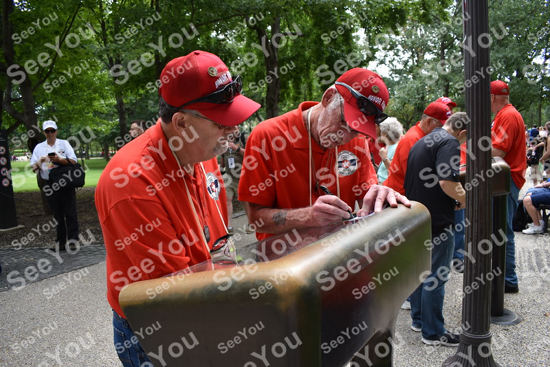 -Messenger photo by Joe Sutter<br /> Rich Almond, Fort Dodge, Army; and Kevin McCarthy, Jackson, Minnesota, Marines; look up names of their fellow soldiers at the directory for the Vietnam Veterans Memorial wall.