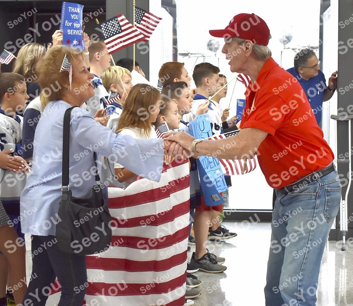 -Messenger photo by Joe Sutter<br /> <br /> Navy Veteran Jimmy Belken, of Alden, shakes hands with Terri Matus as the Reston Raiders hocky team of Reston, Virginia as the Honor Flight veterans arrive to a rousing welcome at Dulles Airport.