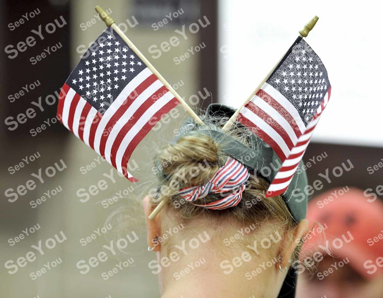 -Messenger photo by Hans Madsen<br /> <br /> Alesha Strain, 13, of Thor, demonstrates her special cap and hair bun flag holding technique Saturday night as she waits for her grandfather, Army veteran Earl Possehn, of Fort Dodge, to return from the Brushy Creek Area Honor Flight at the Fort Dodge Regional Airport.