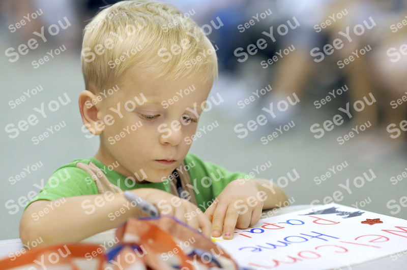 -Messenger photo by Hans Madsen<br /> <br /> William Bodensteiner, 3, of Grand Rapids, Minnesota, works on making a welcome home sign for his grandfather, Army veteran Michael Fritz, of Fort Dodge, who had taken the Brushy Creek Area Honor Flight Saturday.