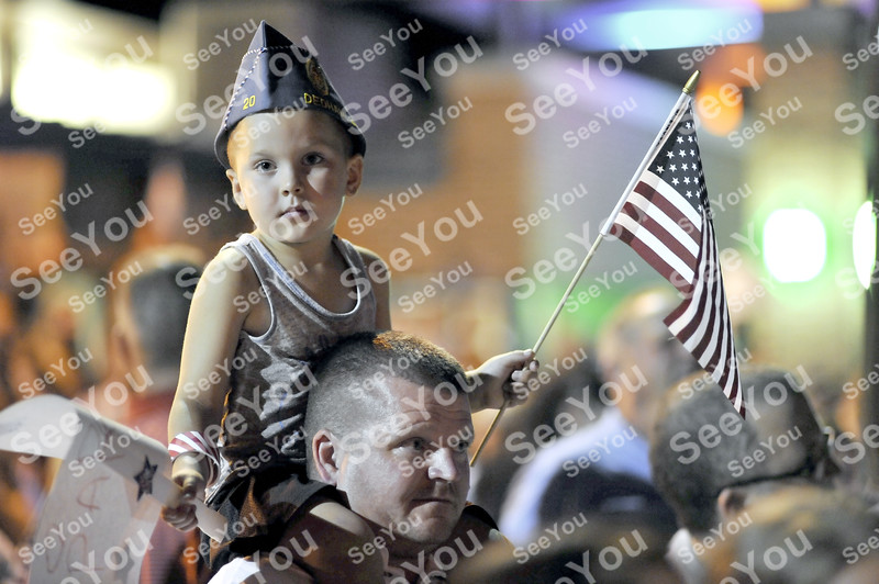 -Messenger photo by Hans Madsen<br /> <br /> Tyran Wolterman, 4, of Templeton, sits on his dad's shoulders Saturday night as they wait for the Brushy Creek Area Honor Flight to land at the Fort Dodge Regional Airport. They were welcoming Army and Navy veteran Dale Wolterman. The hat is Brian Wolterman's Sons of the American Legion cap.