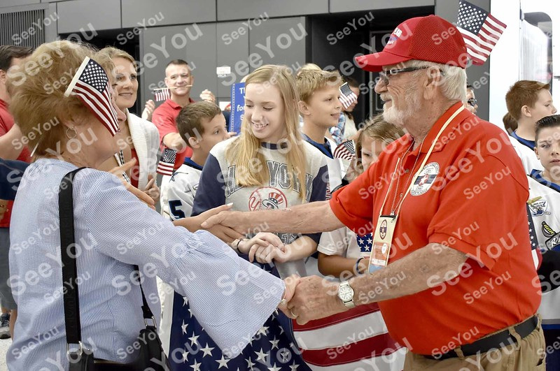 -Messenger photo by Joe Sutter<br /> <br /> Doyle Fry, Navy Veteran, is greeted by Terri Matus, Ella Smith and the Reston Raiders hocky team at Dulles Airport, as the Honor Flight veterans were treated to a welcome by hundreds of volunteers.