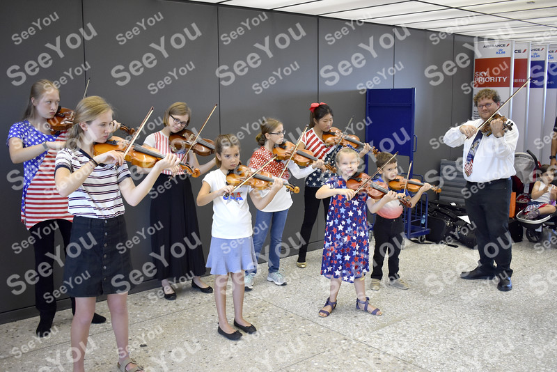 -Messenger photo by Elijah Decious<br /> <br /> LIve musicians, including a group of young violinists and a band, welcome veterans at Dulles International Airport in Washington, D.C.