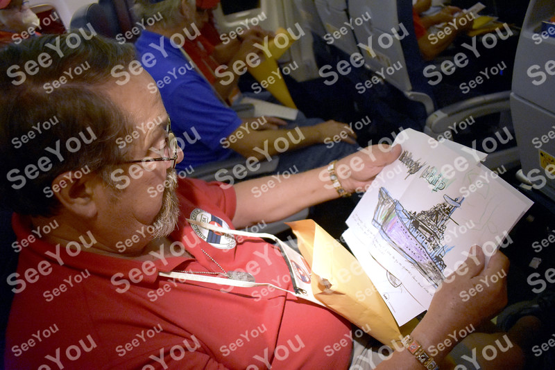 """-Messenger photo by Elijah Decious<br /> <br /> Dave Ricker sorts through the correspondance he received during """"mail call"""" on the flight home."""