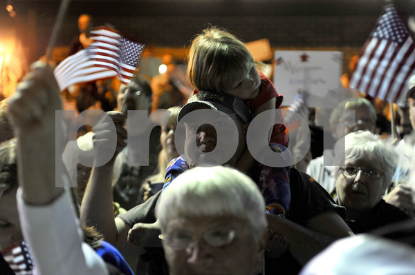 -Messenger photo by Hans Madsen<br /> <br /> Matt Trask, of Renvick, waves his flag as his daughter Bristol Trask, 3, rests on his head Saturday night as they wait for the Brushy Creek Area Honor Flight at the Fort Dodge Regional Airport. They were waiting for Korean War veteran Walter Martin, of Clarion, who served in the Air Force.