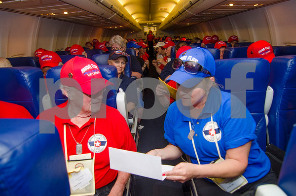 "-Messenger photo by Jesse Major<br /> <br /> Nurse Ann Freser reads a letter to Air Force veteran Bob Stark's loved ones to him on the flight home from Washington, D.C., Saturday. Veterans had ""mail call,"" on the flight to Fort Dodge, where they recieved letters from family and friends."