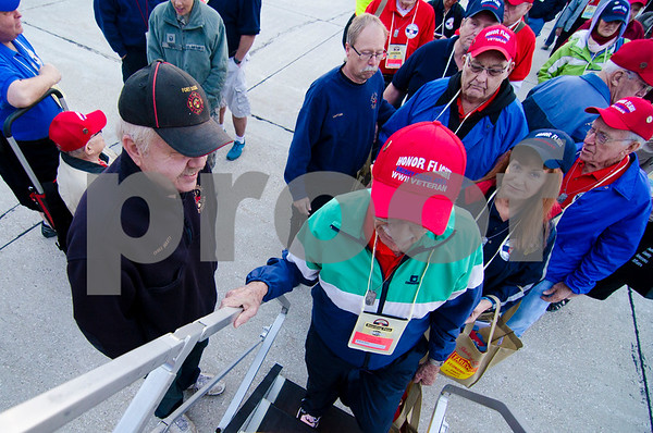 -Messenger photo by Jesse Major<br /> <br /> Fort Dodge Fire Chief Kent Hulett, left, welcomes veterans and guardians as they board their plane to Washington, D.C., for the Brushy Creek Area Honor Flight Saturday.