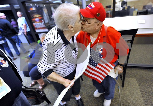 "-Messenger photo by Hans Madsen<br /> <br /> Walter Martin, of Clarion, gets a welcome home kiss from his bride of 62 years, his wife Betty Martin, as he returned on the Brushy Creek Area Honor Flight at the Fort Dodge Regional Airport. Marting served in the Air Force during the Korean War, ""He's my fly boy,"" she said proudly. Her sign read ""Welcome my Hero."""