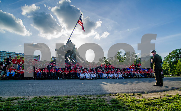 -Messenger photo by Jesse Major<br /> <br /> Area vetrans, guardians and Brushy Creek Area Honor Flight staff sit and stand in the shade of the Marine Corps War Memorial in Washington, D.C., as First Lt. Matt Rojo, Public Affairs officer for the United States Marine Corps Training and Education Command thanks them for serving. He told veterans that because they fought for America in World War II and in the Korean War, his father was able to serve in Vietnam and now he able to serve his country.