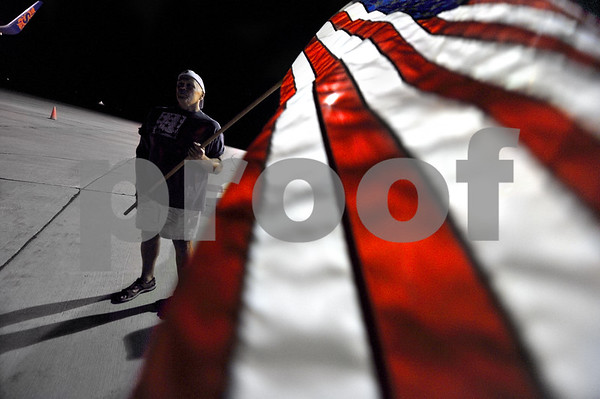 -Messenger photo by Hans Madsen<br /> <br /> Brian Westfall, of Fort Dodge, holds a large American flag Saturday night while greeting returning veterans that were on the Brushy Creek Area Honor Flight. His father in-law, Dewey Ludwig, of Sioux Rapids, was on the flight.