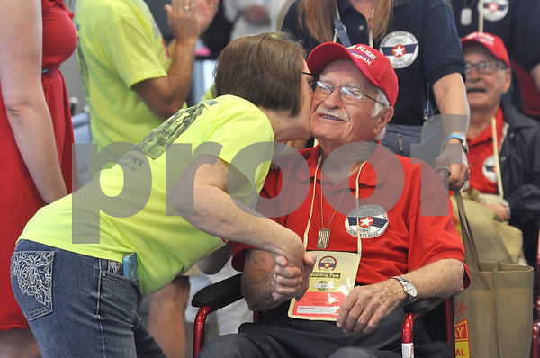 -Messenger photo by Jesse Major<br /> <br /> Robert Starr, a World War II veteran from Clive, smiles as Nancy Hill, a member of the Honor Flight Ground Crew, gives him a kiss as he arrives to Washington Dulles International Air Port on Saturday.