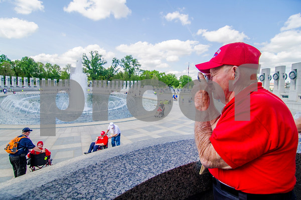 -Messenger photo by Jesse Major<br /> <br /> Army Veteran Robert Speich, of Algona, takes a photo of the National World War II Memorial in Washington, D.C., on Saturday. Most veterans on the Brushy Creek Area Honor Flight had photos of them taken wth the Iowa pillar at the memorial.