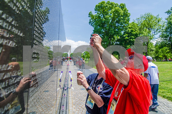 -Messenger photo by Jesse Major<br /> <br /> Paul Schnell, a Navy veteran who served in the Korean War, takes a photo of the name of a relative he has never met that is on the Vietnam Veterans Memorial. Schnell said his family will appreciate seeing the photo.