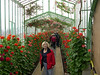 Cindy in one of the passage ways, with flowers hanging from the top of the walkway.