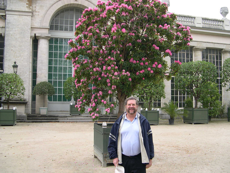 Dick in front of a flowering rose tree in front of the Royal Greenhouses.