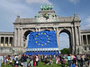 A large EU flag near the arch, held aloft by wind machines.
