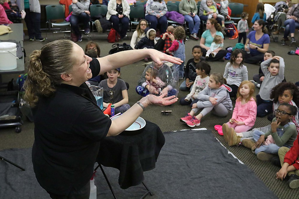 ". Megan Parker with ""Party Bubbles\"" brought her show to the Leominster Public Library on Thursday afternoon for a packed house of kids and parents. She showed she could make a bubble with her hands. SENTINEL & ENTERPRISE/JOHN LOVE"