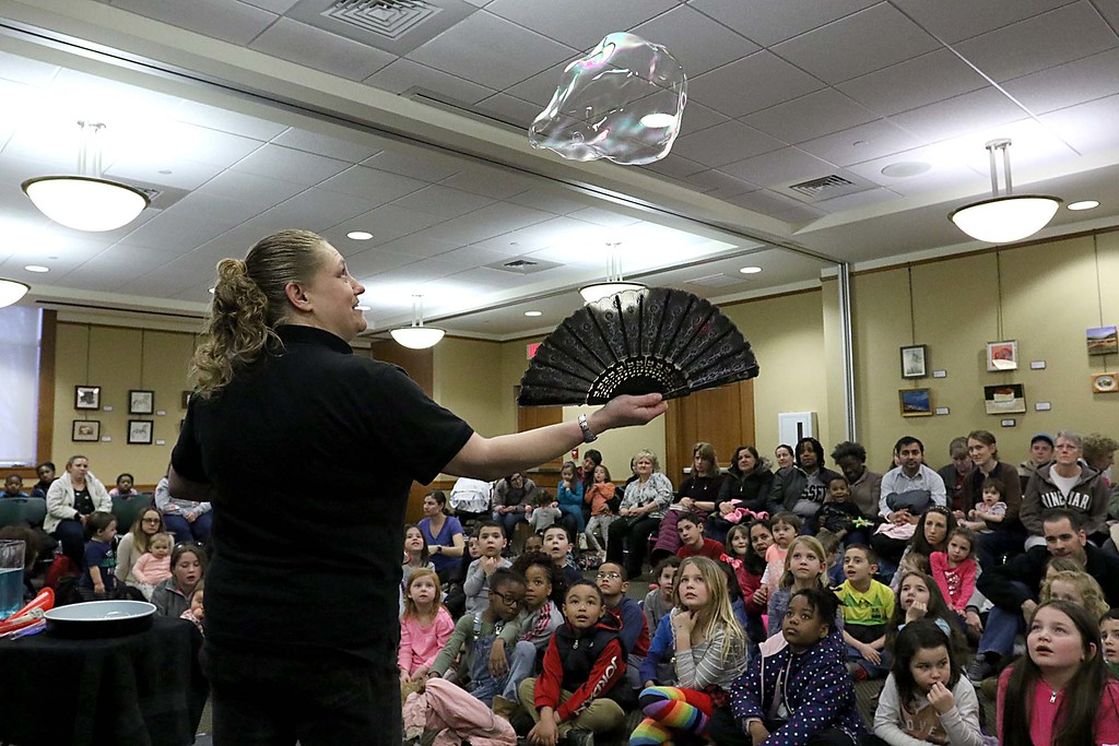 ". Megan Parker with ""Party Bubbles\"" brought her show to the Leominster Public Library on Thursday afternoon for a packed house of kids and parents. The kids gathered around on the floor to watch her play with the bubbles. here they watched as she used a fan to keep the bubble afloat. SENTINEL & ENTERPRISE/JOHN LOVE"
