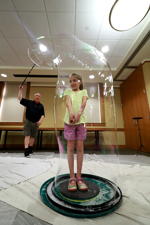 . Keith Johnson from Rhode Island was at the Leominster Public Library on Tuesday with his show and knowledge of bubbles. At the end of Johnson\'s show he put one lucky audience member in a bubble. That lucky person was Cailyn Kindorf, 7, from Sterling. SENTINEL & ENTERPRISE/JOHN LOVE