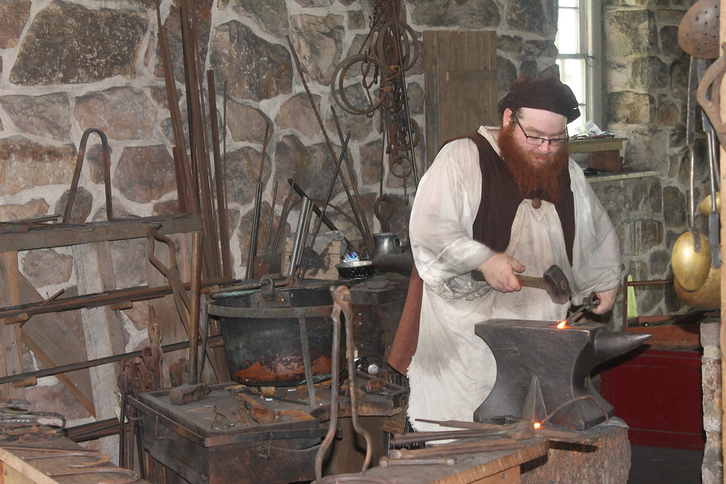 . Demonstrating the 18th century trade of metal working inside the Blacksmith Shop.