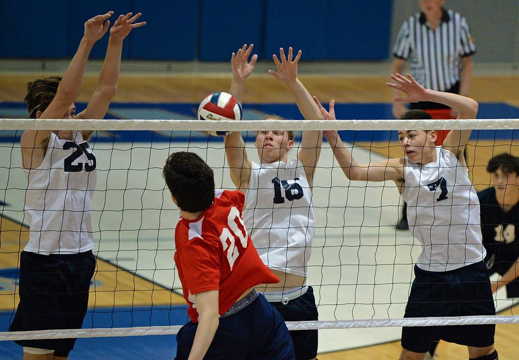. Jack Gunshenan (25), Keven D\'Arcy (16) and Justin Burns (7) play tough at the net. (photo by John Gleeson)