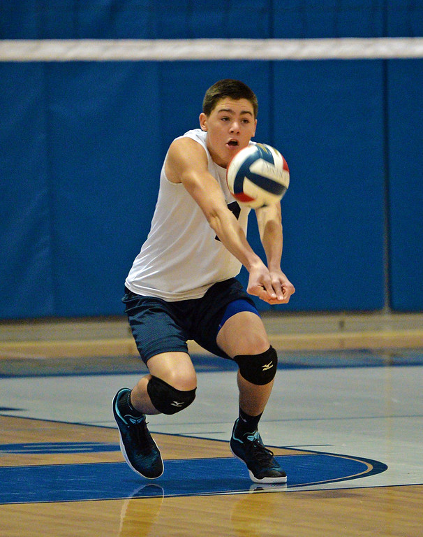 . Justin Burns (7) digs out a low serve. (photo by John Gleeson)