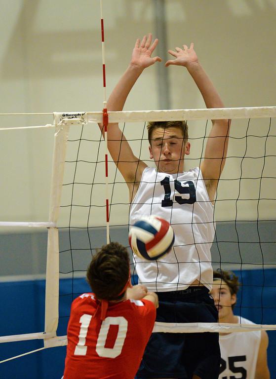 . Nick Baniewicz (19) rejects shot at net. (photo by John Gleeson)