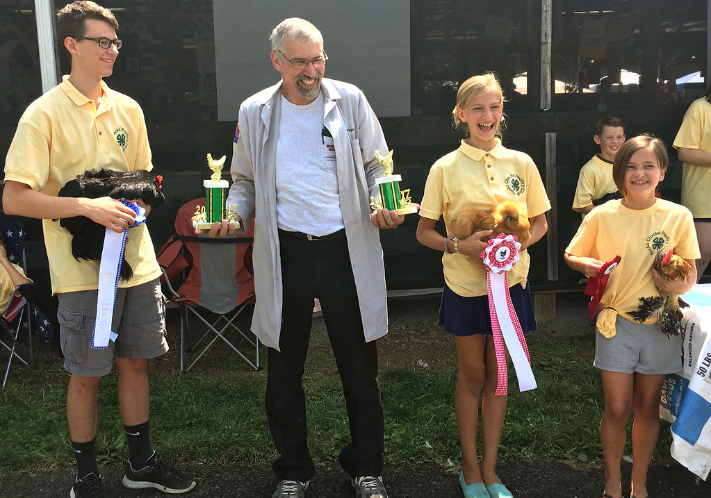 . A judge awards the Grand Champion Award in the poultry showmanship division to Jake Monson of Doylestown, left, and the Reserve Champion Award to Mary Katherine Hackenberg of Doylestown. Sadie O\'Donnell, right, of Quakertown, was recognized with a third place award. They are all members of the Bucks Clucks.